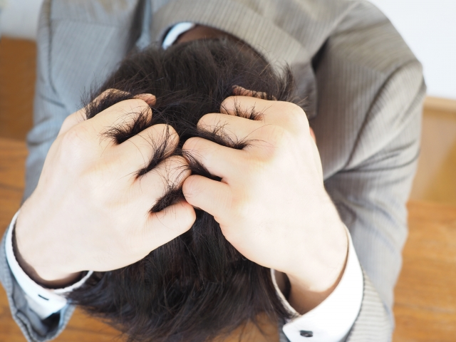 頭を抱える男性